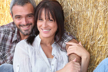 Farming couple sitting in the hay photo