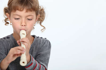 tuneful: Girl playing a recorder Stock Photo