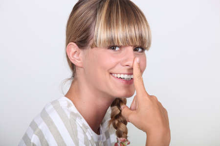 Woman with finger on her nose Stock Photo - 12914813