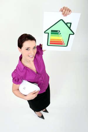 energy ranking: Female architect holding energy rating card
