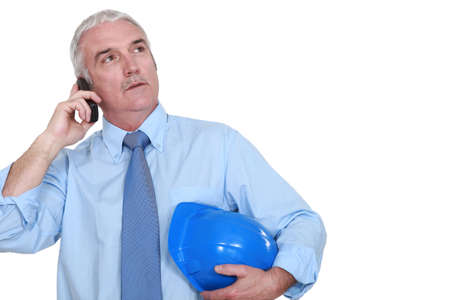 middle-aged foreman making a call hard hat in hand Stock Photo - 12912030