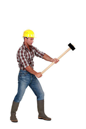 pounding head: Man using sledge-hammer