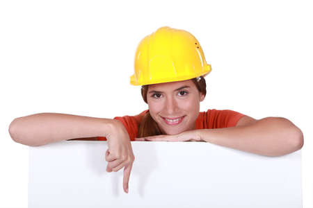downwards: Female construction worker pointing to blank poster