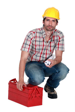 Builder carrying plans and a toolbox photo