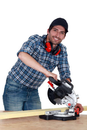 A carpenter with a circular saw  photo