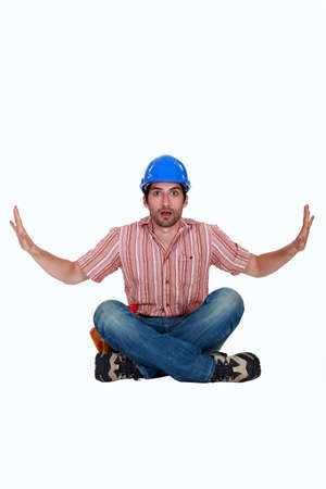 bewildered: Surprised laborer sitting on white background Stock Photo