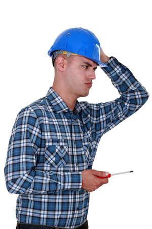 dubious: A dubious handyman with a screwdriver