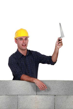 Stonemason holding up a trowel photo