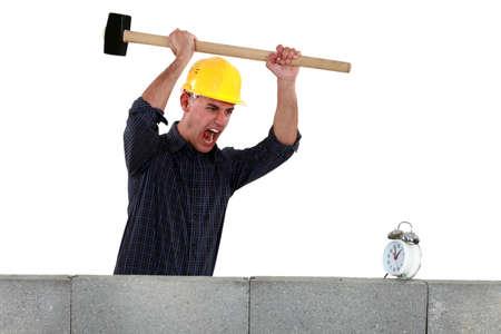 Tradesman about to smash an alarm clock Stock Photo - 12911494