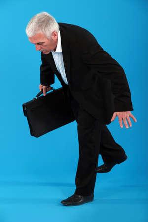 tripping: A mature businessman off balance  Stock Photo