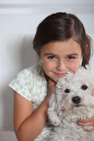 Little girl holding small white dog photo