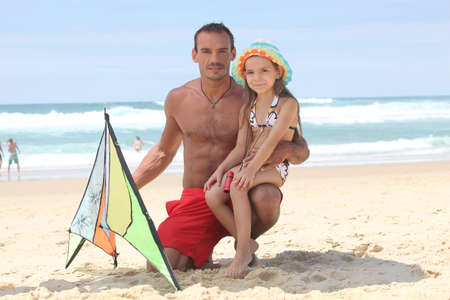 Man and little girl playing with kite at the beach photo