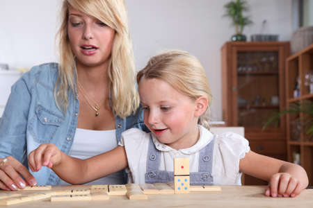 25 years old: Young woman and her daughter playing dominoes