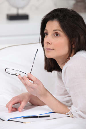 Woman writing in bed photo