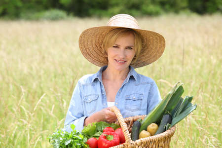 Woman in straw hat with basket of vegetables walking through a field photo