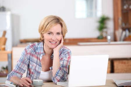 tarde de cafe: Una mujer mirando a su ordenador portátil mientras se toma una taza de café Foto de archivo