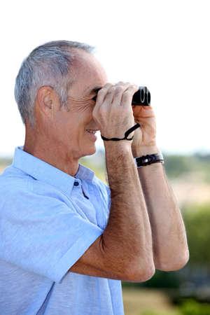75s: senior man looking through binoculars Stock Photo