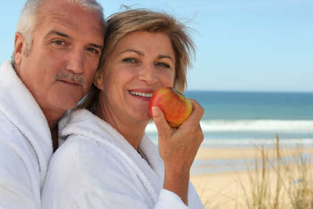 55 59 years: Mature couple in bathrobes eating an apple on the beach Stock Photo