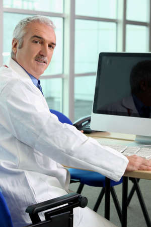 Doctor sat at computer photo