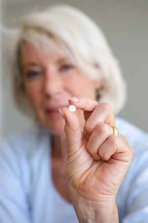 Older woman holding a pill photo