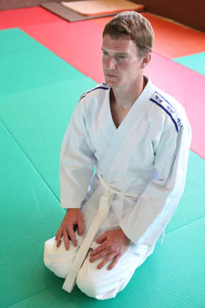 kneeling man: Kneeling man on judo mat