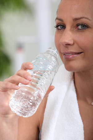 Woman drinking water after sport photo
