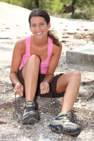 두서없는: 여자 야외 매는 신발 끈을 앉아 스톡 사진