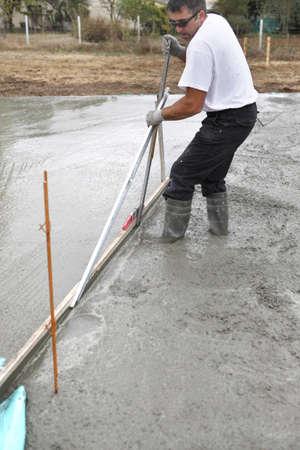 Man spreading concrete foundation photo