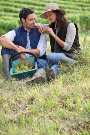 Couple of grape pickers sat on the grass photo