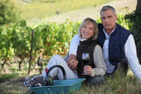 couple of radiant wine-growers posing in vineyards photo