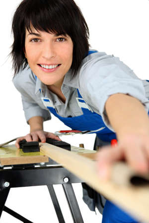 servicewoman: Female carpenter using workbench