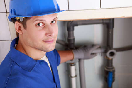 Young male plumber installing pipes photo