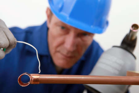 soldering: skilled tradesman in blue jumpsuite is soldering a copper pipe