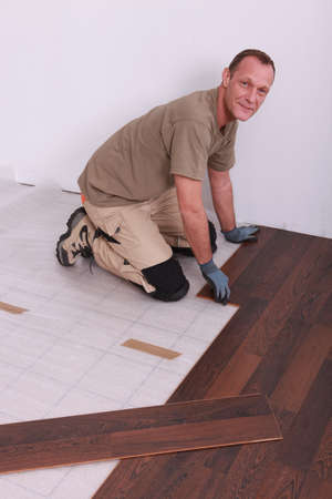 Man laying wooden flooring photo