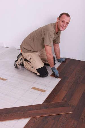 Man laying wooden flooring photo