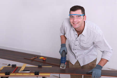 tongue and groove: Man cutting tongue and groove floorboards with a jigsaw Stock Photo