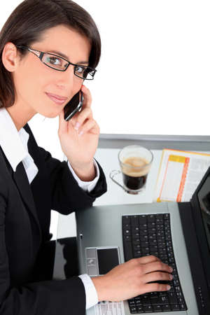 Woman at laptop with coffee and cellphone photo