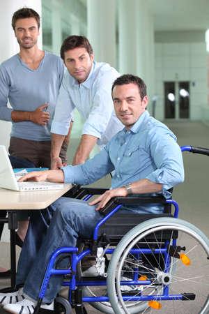 accessibilit�: L'uomo in sedia a rotelle nella foto con i colleghi Archivio Fotografico