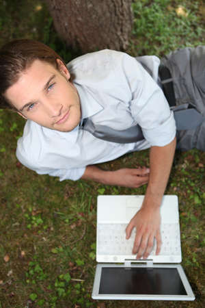 Top view of man laid by tree with laptop Stock Photo - 12499776