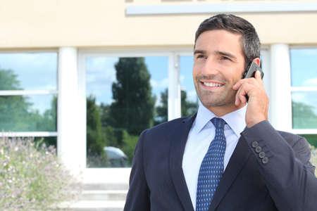 caucasico: Hombre sonriente en traje hablando por tel�fono m�vil Foto de archivo