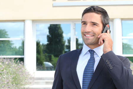 approachable: Smiling man in suit talking on cellphone Stock Photo