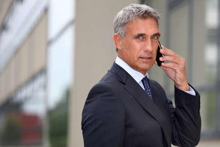 Mature businessman using a cellphone outside photo