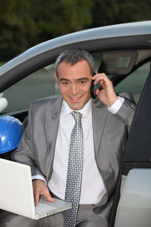 sell car: Architect in car speaking on mobile telephone
