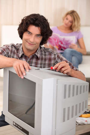 Man fixing an old television photo