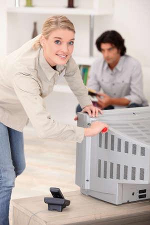 servicio domestico: La mujer de retirar la parte posterior de un aparato de TV