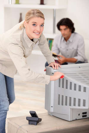 cathode ray tube: Woman removing the back of a tv set Stock Photo