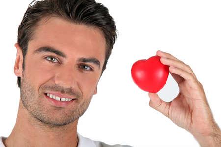 curare teneramente: Ritratto di un uomo che tiene un cuore
