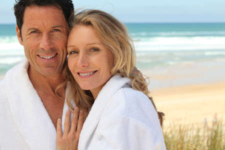robes: Couple stood by the sea wearing bathrobes