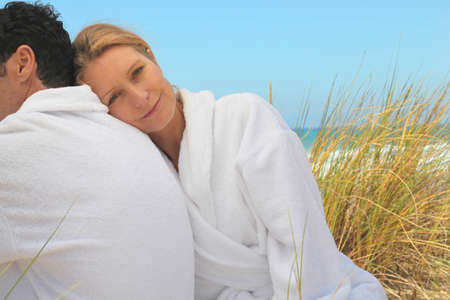 toweling: Couple sitting in the sand dunes in white toweling robes