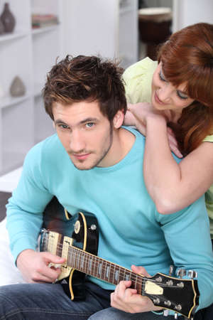 Young couple at home with a guitar Stock Photo - 12500616